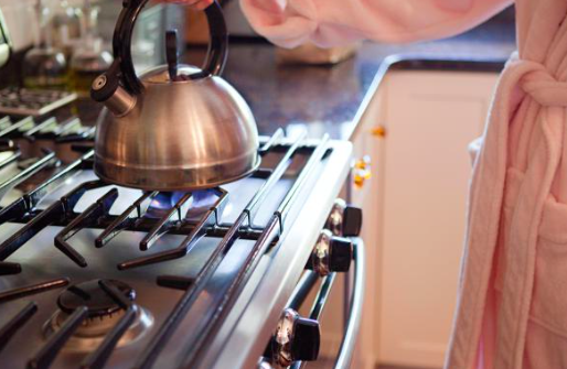Woman places kettle on gas hob